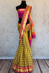 90B342 Buy this chanderi cotton silk Indian saree online at our ethnic fashion store - Pure Elegance. The checked yellow sari with pops of golden, pink & orange is a lovely pick for Indian weddings & parties.