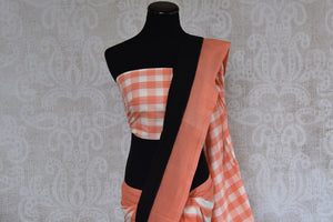 90B392 This striped orange, white & black cotton ikkat saree, available at our Indian clothing store online in USA, is refreshingly unique. The party wear saree will be a great addition to your ethnic wear wardrobe.