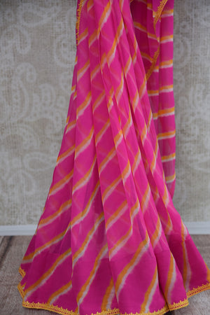 90B398 Gorgeous leheriya saree in a pink & yellow color combination with yellow blouse, great for Indian wedding functions like mehendi functions and festive occasions. The chiffon saree from India can be bought online at our online Indian fashion website - Pure Elegance.