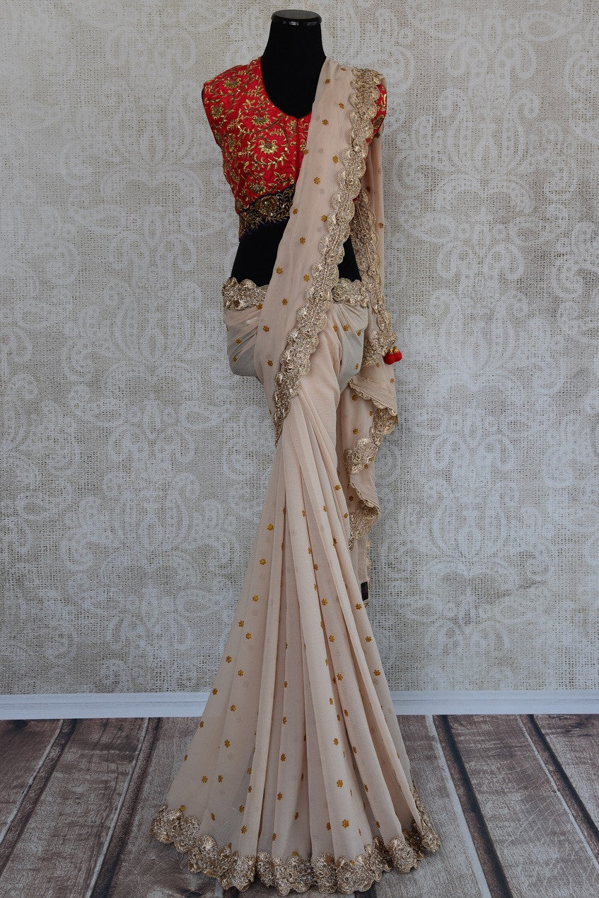90b450 Embroidered chiffon sari with raw silk red designer blouse available at Pure Elegance. This beige saree hasa lovely gold lace border and zari embroidery perfect for parties and functions.