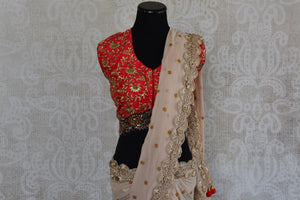 90b450 Embroidered chiffon sari with raw silk red designer blouse available in USA at our store Pure Elegance. This beige saree has an elegant gold lace border and zari embroidery perfect for parties and functions.