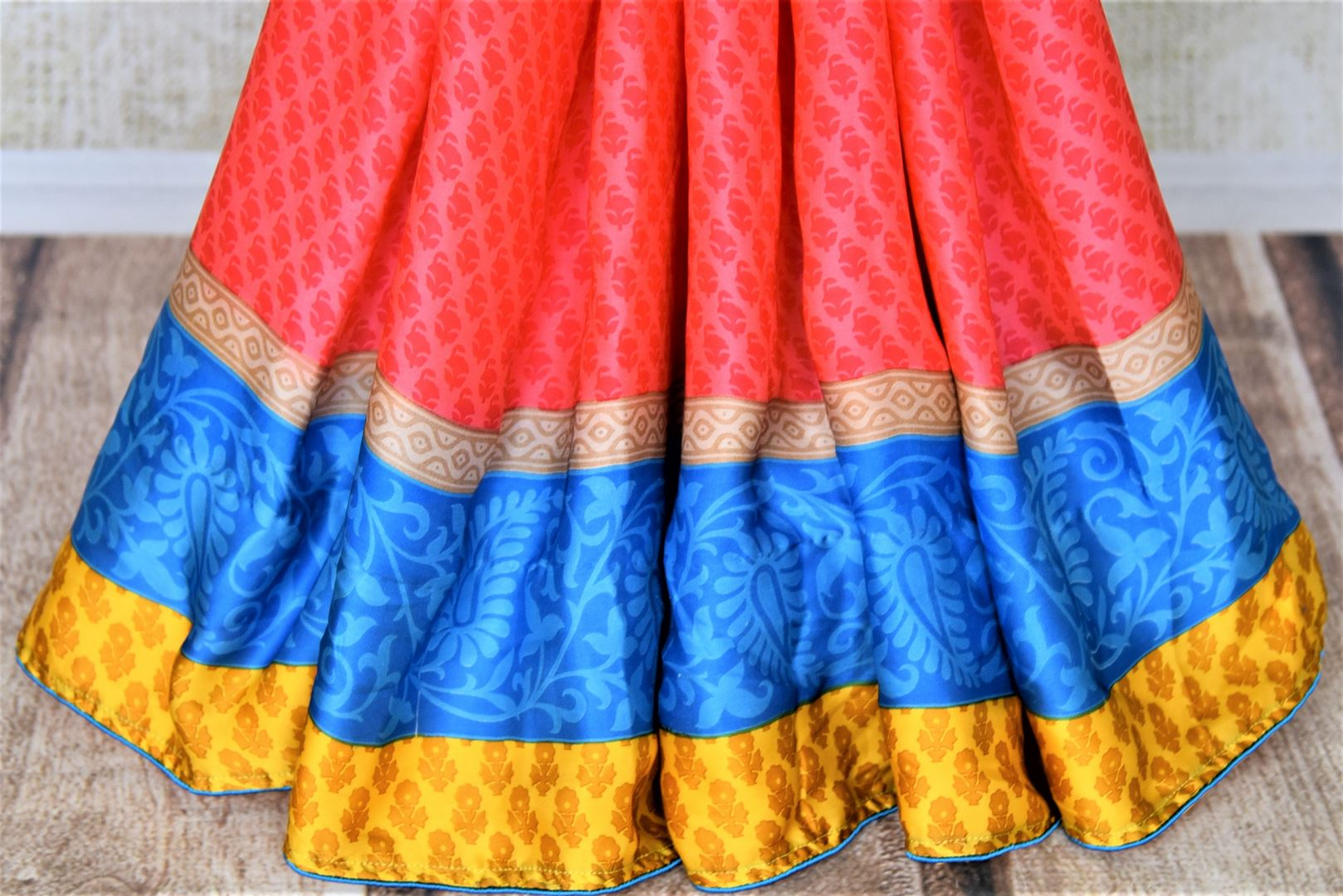 Buy salmon pink prined crepe saree online in USA with blue and yellow border. Elevate your ethnic style on weddings and festive occasions with stunning designer sarees, pure silk sarees, crepe sarees, printed sarees from Pure Elegance Indian fashion boutique in USA.-pleats