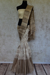 90b559 White and beige traditional kora silk saree with floral pattern. The beautiful Indian saree can be worn at Indian weddings, ethnic festive occasions and pujas. Simple, and alluring, you'll love having this Indian outfit in your wardrobe.