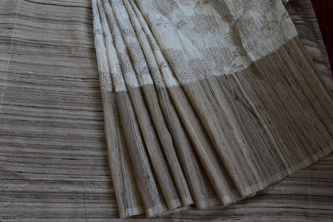 90b559 White and beige traditional kora silk saree online in USA with floral pattern. The beautiful Indian saree can be worn at Indian weddings, ethnic festive occasions and pujas. Simple, and alluring, you can but it at our store Pure Elegance.