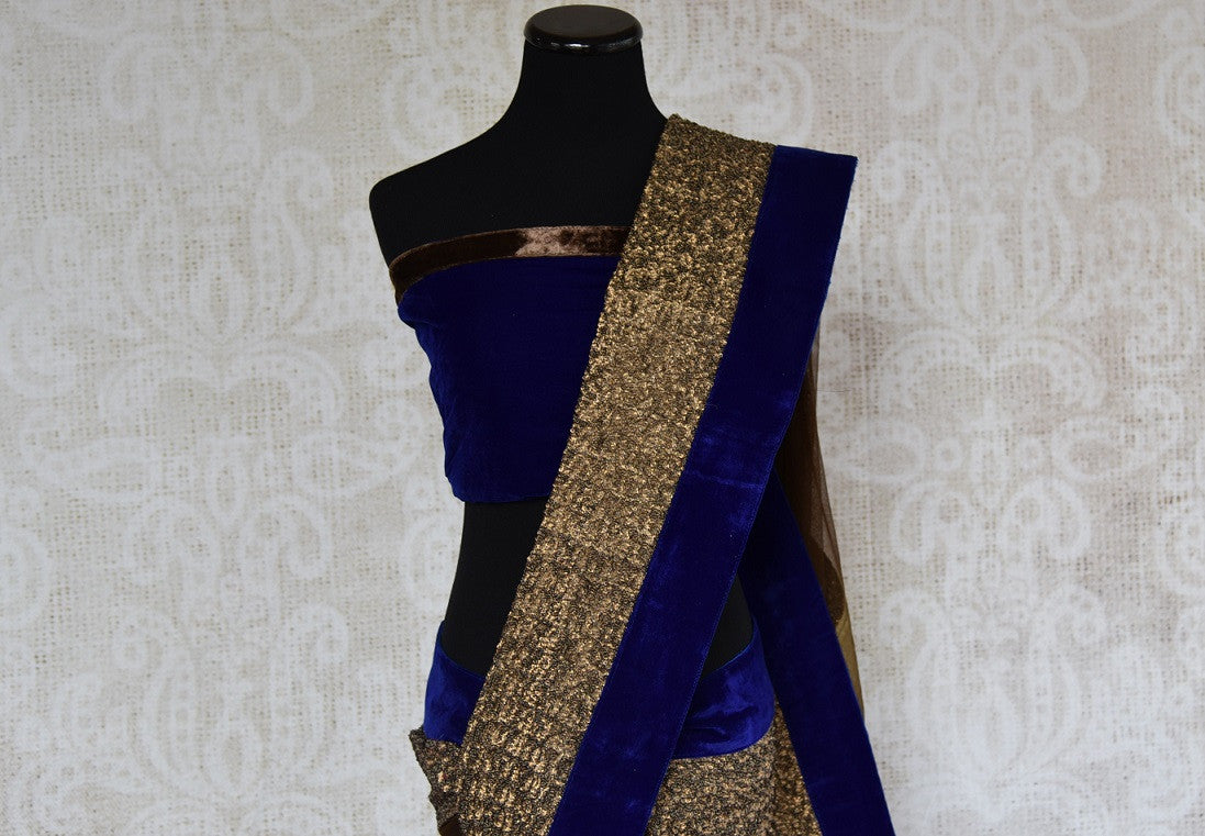 90B577 Half georgette, half net saree with a rich velvet border and a thick golden trim, available online at our store Pure Elegance, USA. The brown and blue sari makes for the perfect ethnic party wear outfit for this season!