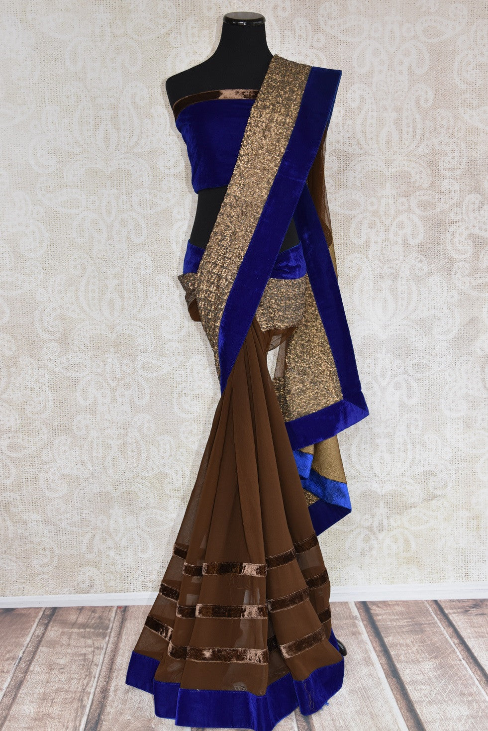 90B577 Half georgette, half net saree with velvet border and thick golden trim, available online at Pure Elegance, USA. The brown and blue sari makes for the perfect Indian party wear outfit for this season!