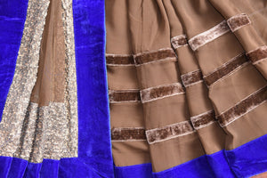 90B577 Half georgette, half net saree with velvet border and thick golden trim. The brown and blue sari makes for the perfect Indian party wear outfit and is available online at Pure Elegance, USA.