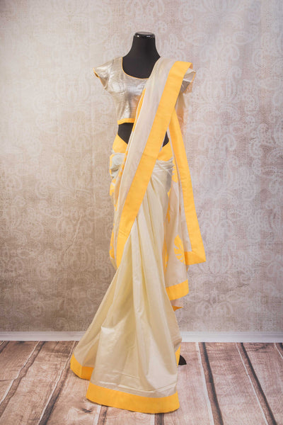 90b628 Pure silk golden saree with bright yellow striped pallu and leaf pattern. The party wear saree can be bought online at our Indian clothing store online in USA and comes with a silver embellished blouse.