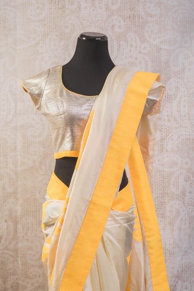 90b628 Pure silk party wear saree with bright yellow striped pallu and leaf pattern with stitched silver embellished blouse. Buy this striking saree from India online at our Indian clothing store online in USA.
