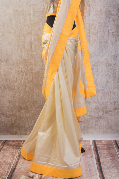 90b628 Pure silk golden saree with a vibrant yellow striped pallu with leaf pattern & a stitched silver embellished blouse. Buy this party wear saree online in USA at Pure Elegance.