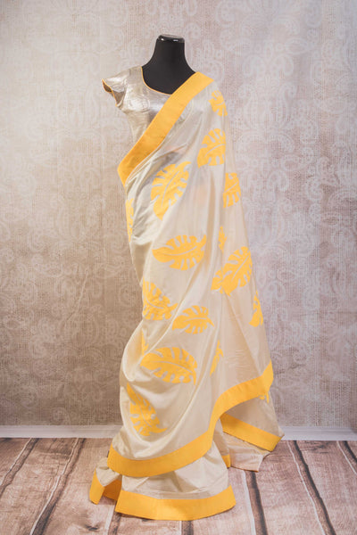 90b628 Lovely golden saree with bright yellow striped pallu with leaf pattern & stitched silver embellished blouse. The pure silk saree can be bought online at Pure Elegance and makes for a great ethnic outfit for party wear.