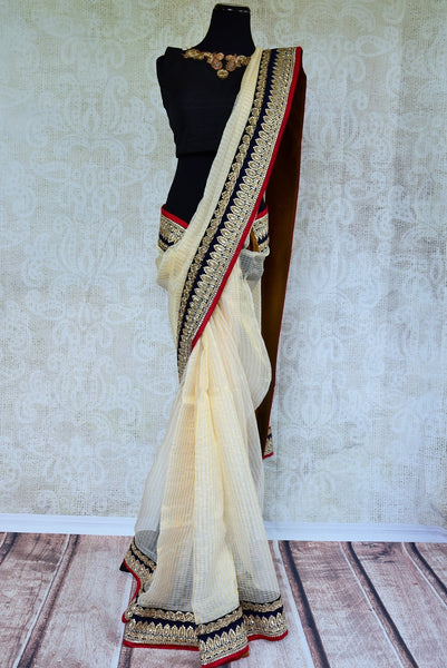 90B694 Traditional Zari kota saree with zardozi embroidery and sequined border. Buy this classic cream, black & red Indian outfits from Pure Elegance - our Indian wear store online in USA.