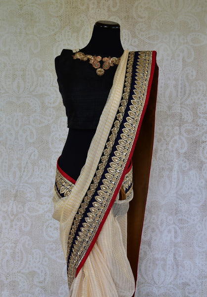90B694 Traditional zari kota saree from India with gorgeous zardozi embroidery and sequined border. Buy this elegant cream, black & red saree from Pure Elegance - our Indian wear store online in USA.