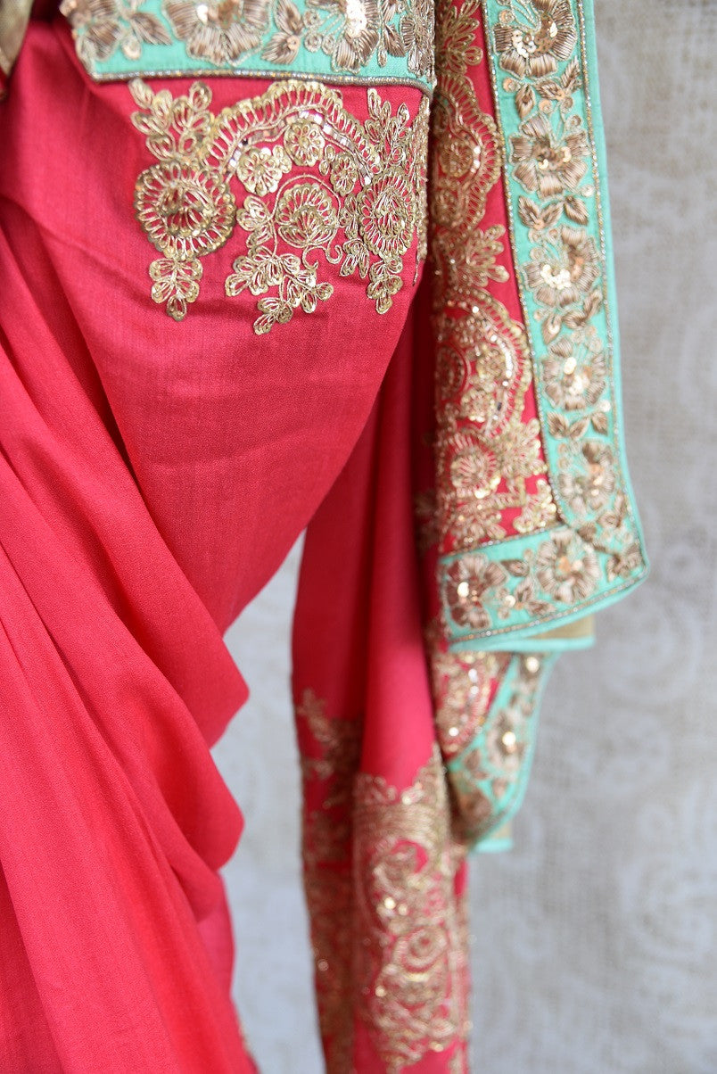 90b747 A refreshing color combination of pastel red & blue meets intricate embroidery in this tissue georgette saree. The heavy sari, available online at Pure Elegance makes for an ideal Indian outfit for weddings and is sure to turn heads where ever you go!