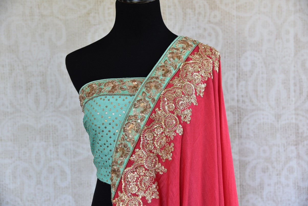 90b747 Lovely pastel red georgette tissue saree with blue border trim and blouse and traditional embroidery. The classic Indian saree available online at Pure Elegance makes for an ideal ethnic outfit for weddings!