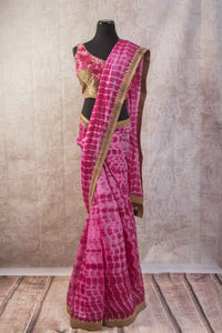 90b806 Tie dye saree with an embroidered blouse and border. The beautiful pink Indian sari online at Pure Elegance is wonderfully versatile and can be worn to parties and Indian weddings, sangeets, receptions and pujas.