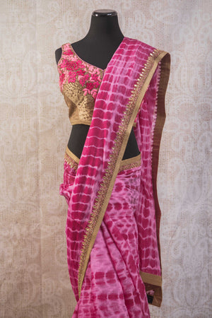 90b806 Classic tie dye saree with an embroidered blouse and border available online at Pure Elegance. The beautiful pink Indian sari is wonderfully versatile and can be worn to parties and Indian weddings, sangeets, receptions and pujas.