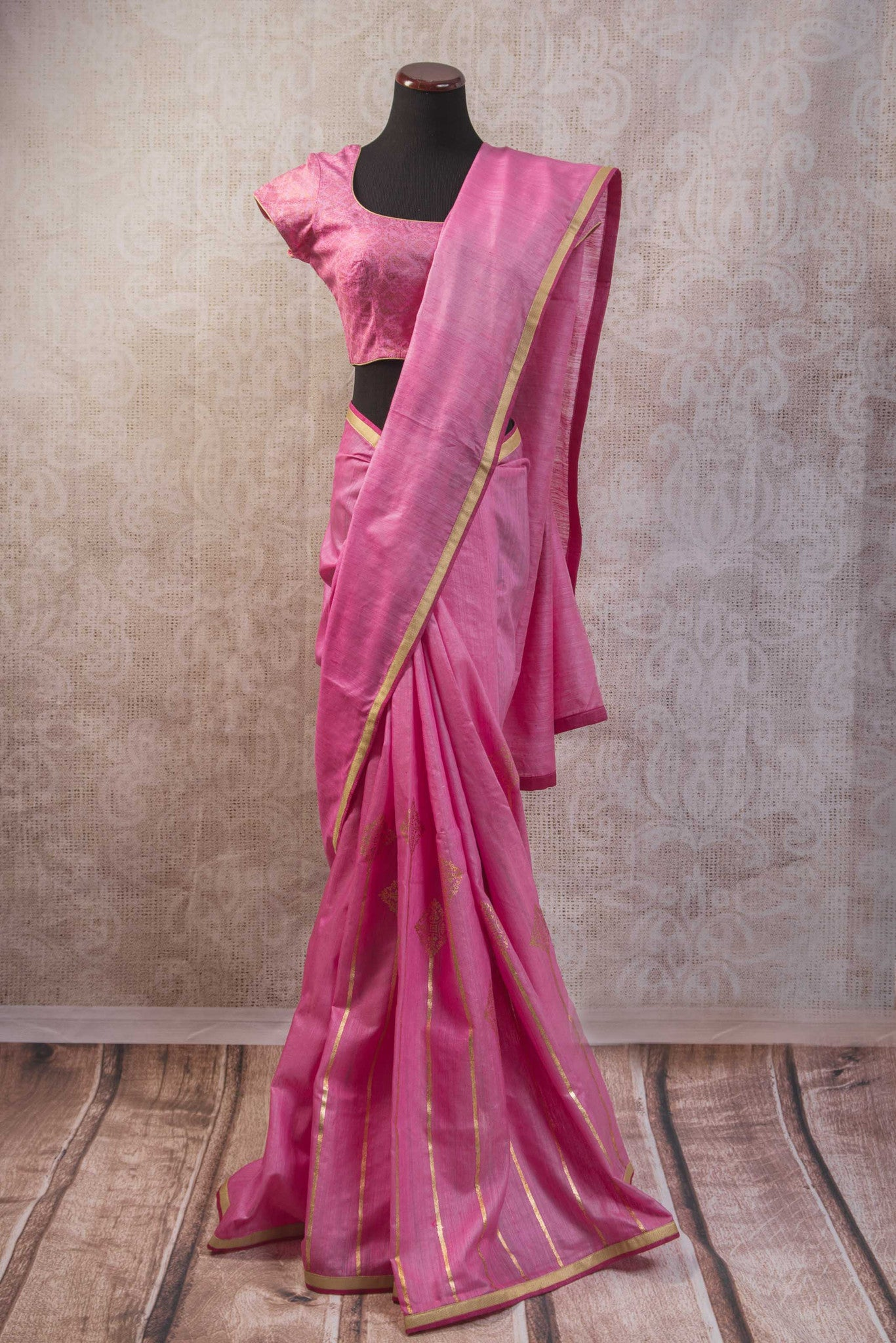 90b839 Matka silk saree with khari print and golden border. This lovely pink saree comes with stitched blouse and can be bought online at our ethnic clothing store in USA and is perfect for Indian wedding and functions.