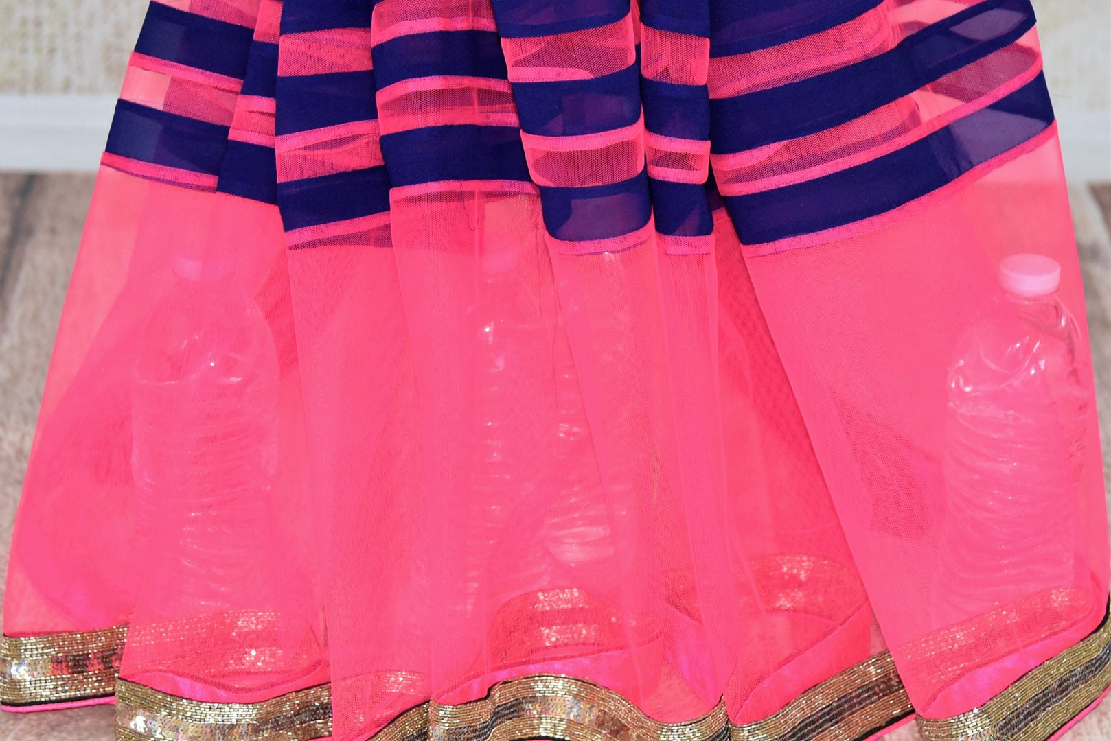 Buy dark blue georgette saree online in USA with pink embroidered net border from Pure Elegance. Let your ethnic style be one of a kind with an exquisite variety of Indian handloom sarees, pure silk sarees, designer sarees from our exclusive fashion store in USA.-pleats