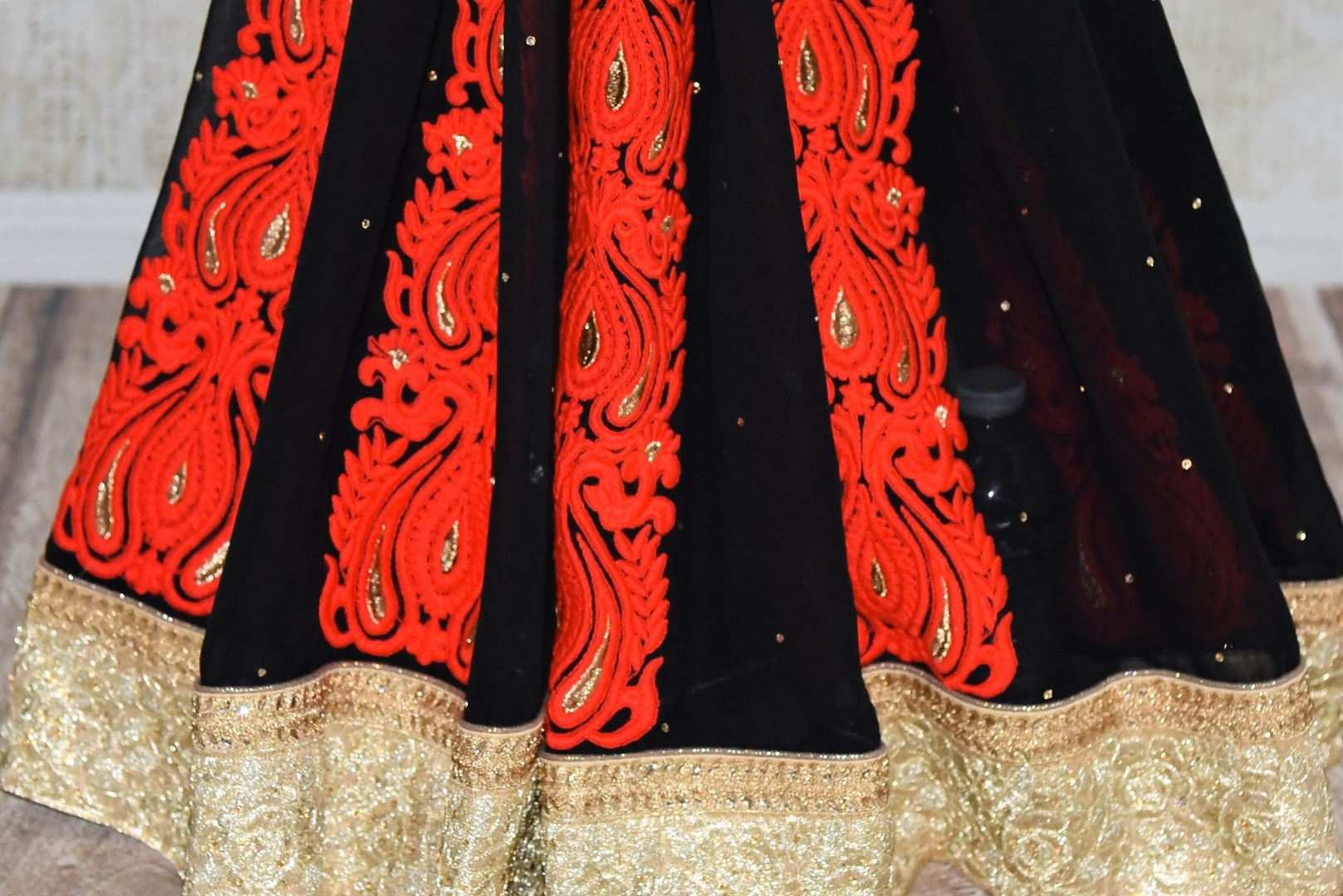 Shop black georgette saree online in USA with embroidered gold border from Pure Elegance. Let your ethnic style be one of a kind with an exquisite variety of Indian handloom sarees, pure silk sarees, designer sarees from our exclusive fashion store in USA.-pleats