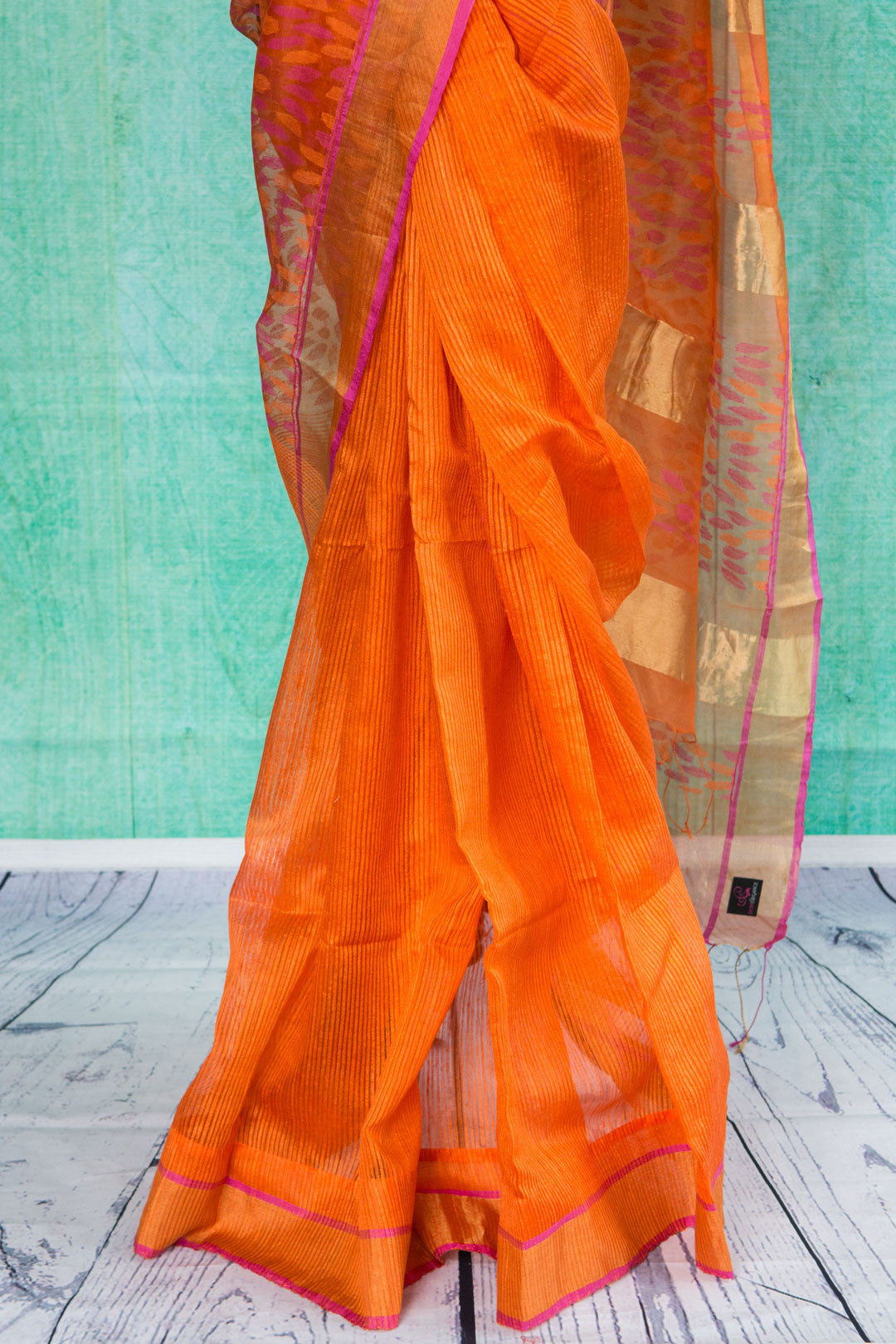 90c009 Bright orange saree with a golden border with pink trim. Buy this classic matka silk saree, ideal for festive occasions at Pure Elegance, our Indian clothing store in USA. This one's a saree for all seasons and occasions!