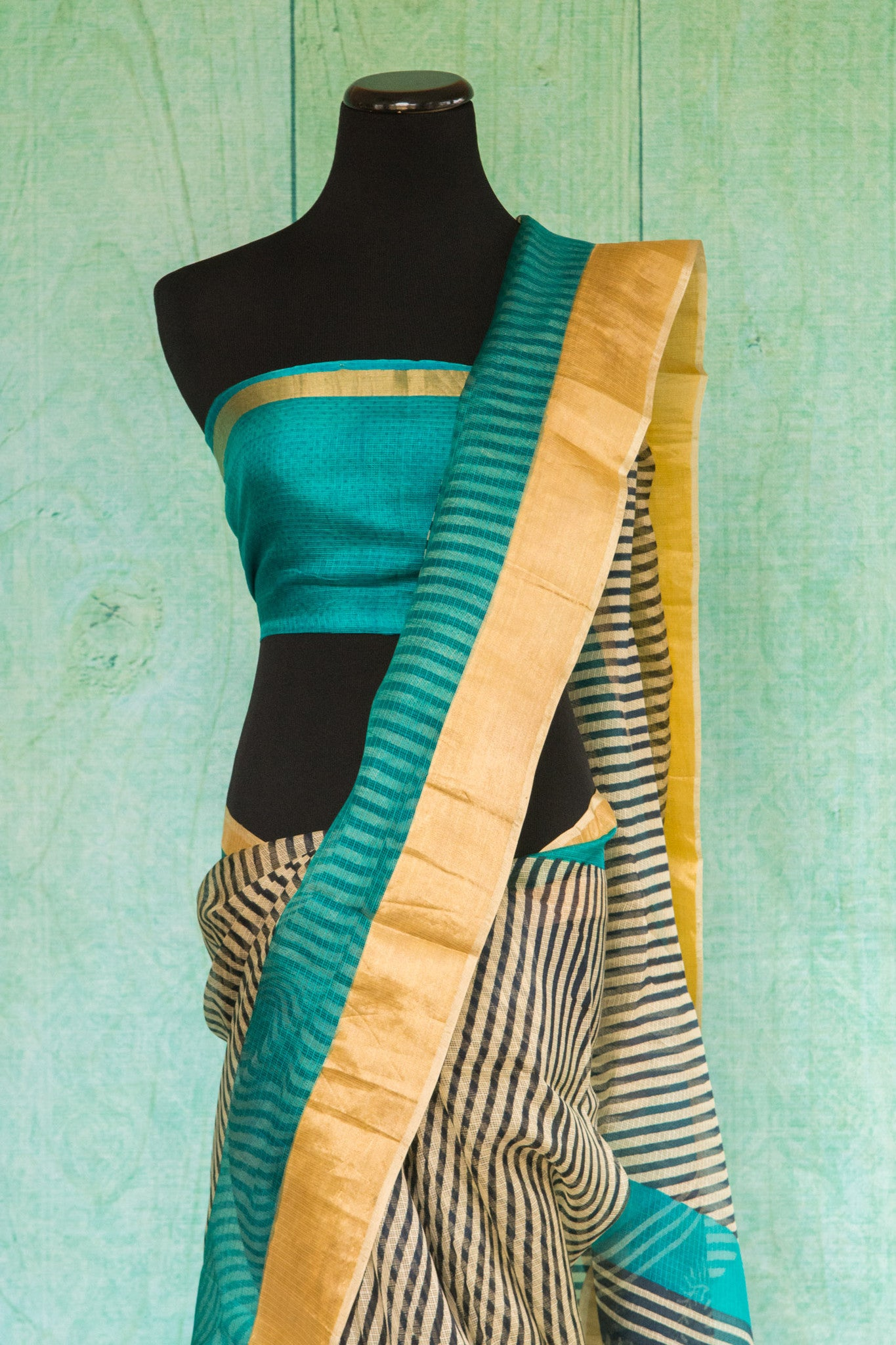 90c085 Black and cream striped zari kota saree with pops of blue and golden. This printed party wear saree can be bought at Pure Elegance - our Indian clothing store online in USA. The beautiful sari is sure to flutter hearts!