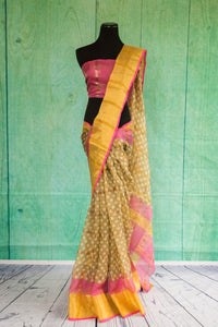 90c087 Traditional, golden, pink and yellow sari available at our Indian wear store in USA. The polka dotted zari kota saree is perfect for pujas and festive occasions. The vibrant sari is absolutely swoon-worthy!
