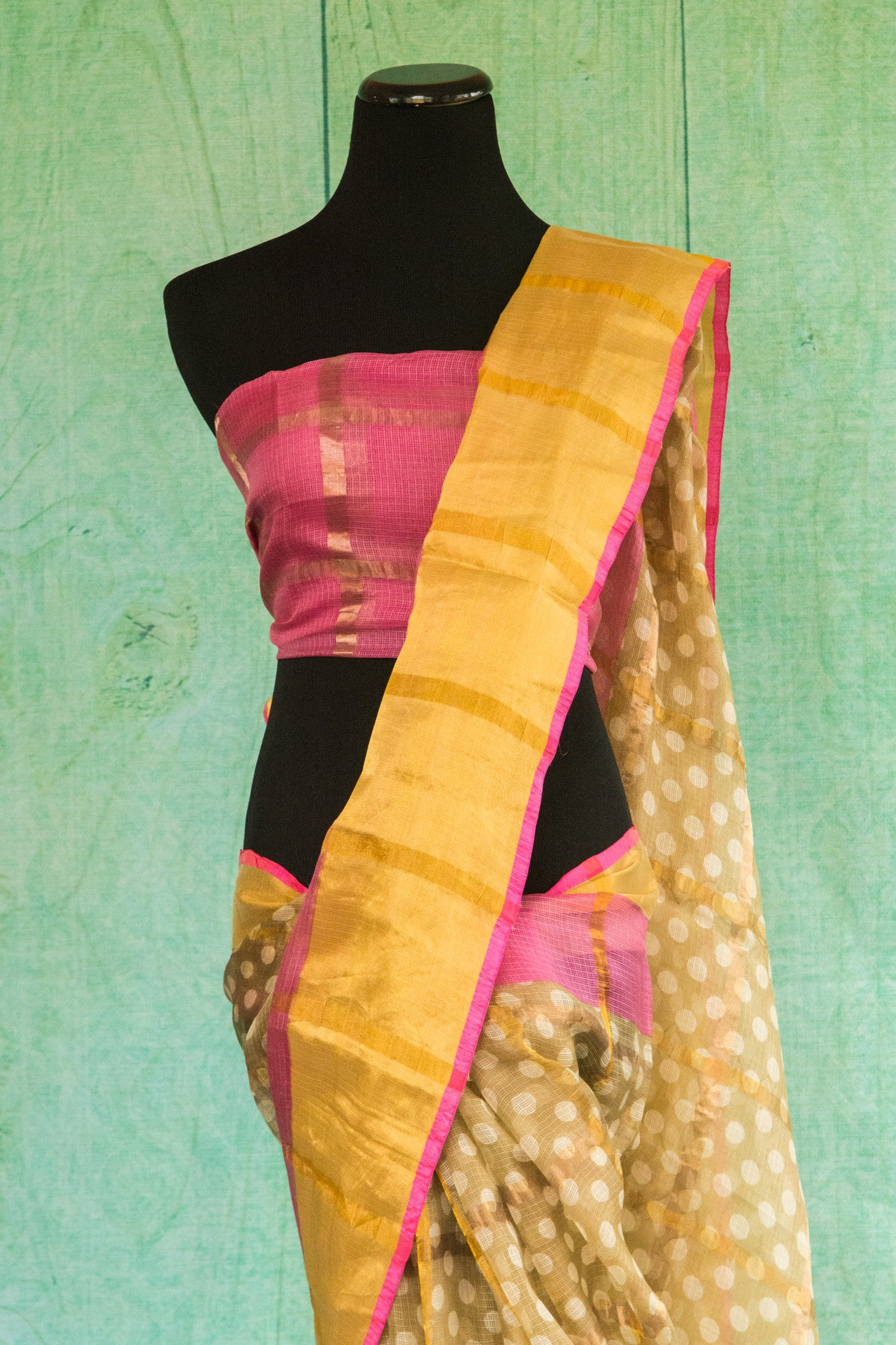 90c087 Traditional printed zari kota saree available at our Indian wear store in USA. The yellow saree with pops of pink and gold is perfect for pujas and festive occasions. The vibrant sari is absolutely swoon-worthy!