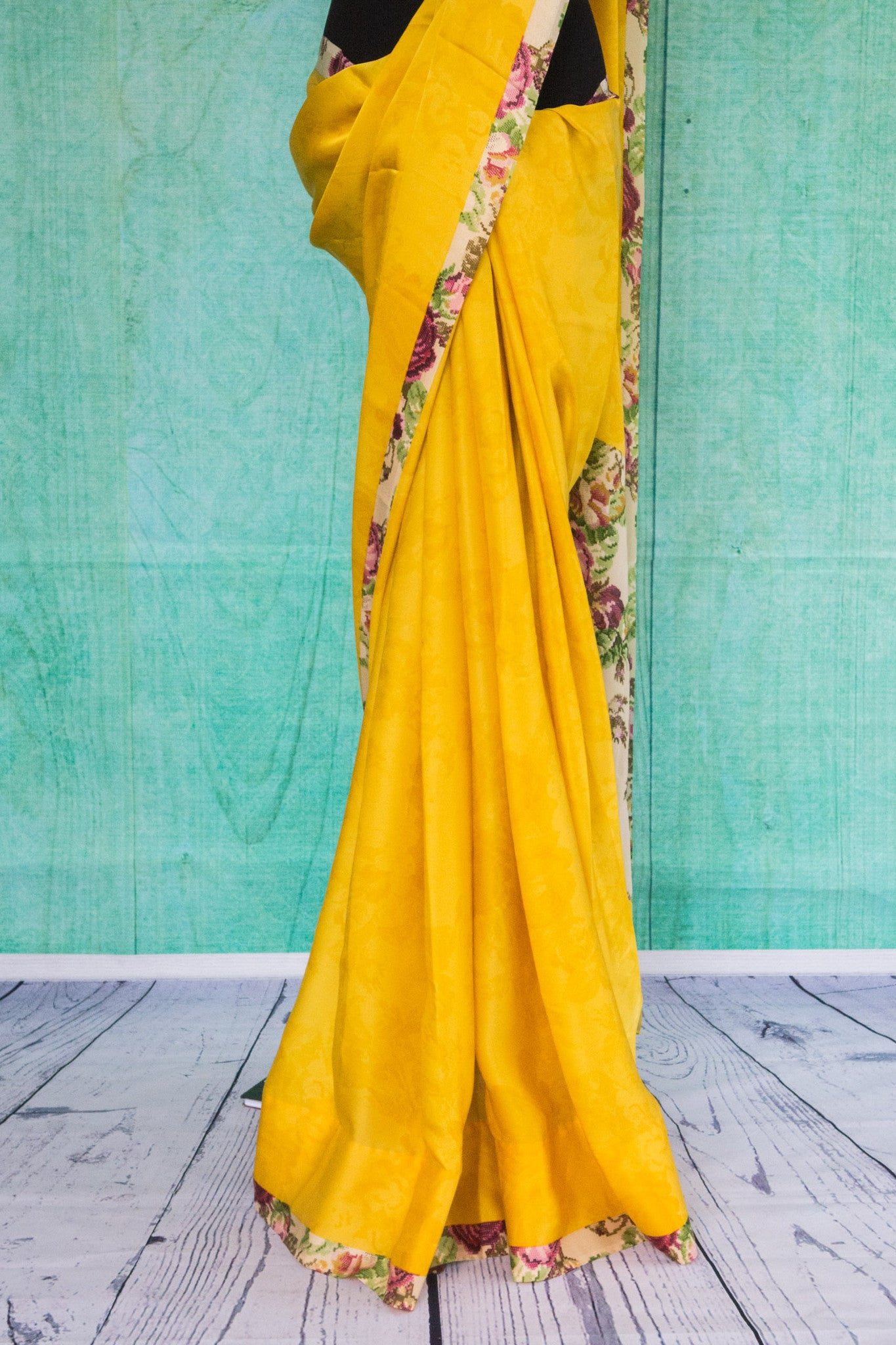 90c092 Plain yellow saree with an elegant floral blouse and border trim, perfect for ethnic festivities. Buy this satin crepe saree in USA at our Indian wear store Pure Elegance.
