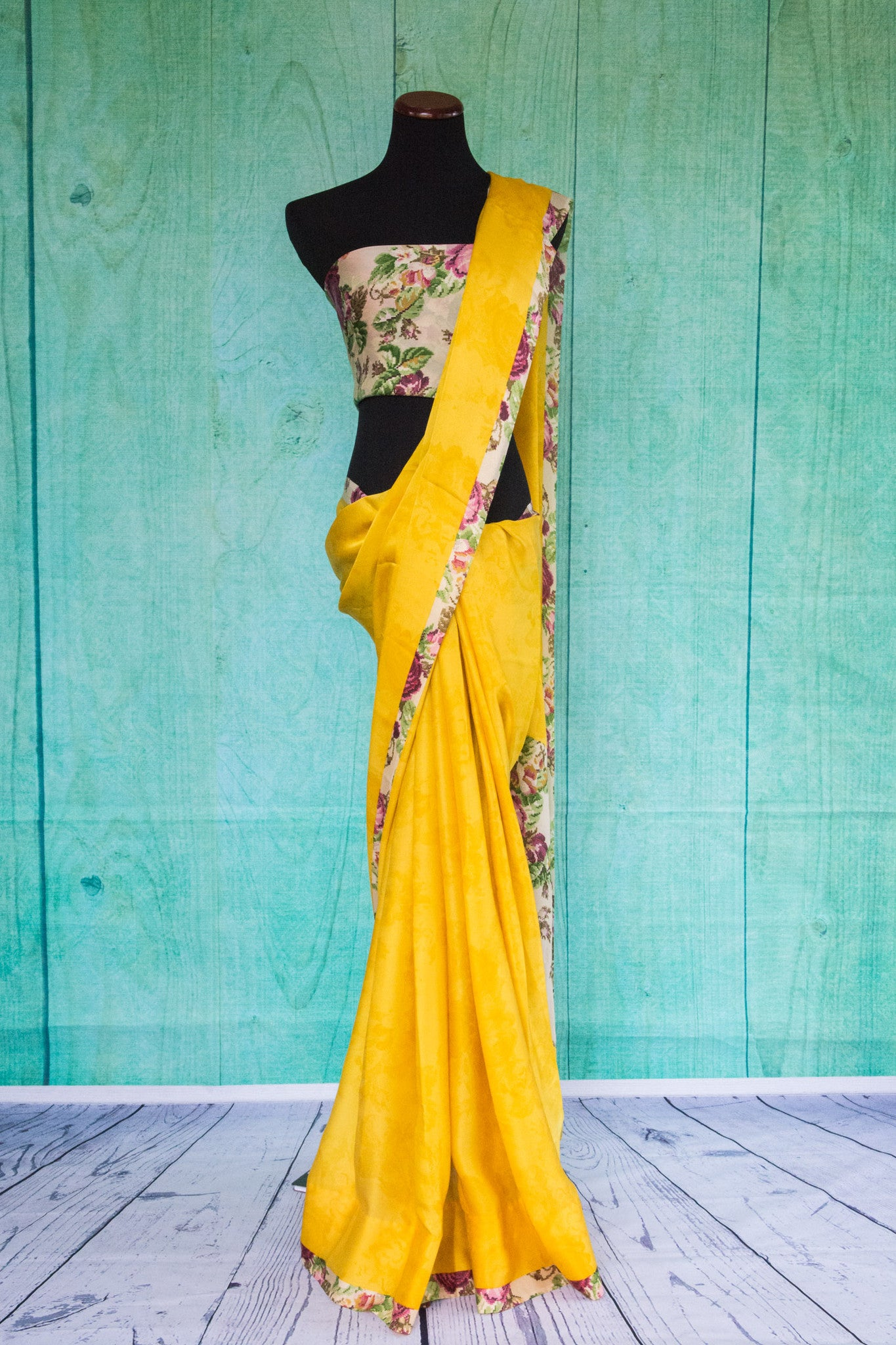 90c092 Yellow plain saree with floral blouse and border trim ideal for festive occasions and pujas. Buy this satin crepe saree online in USA at our ethnic clothing store Pure Elegance.