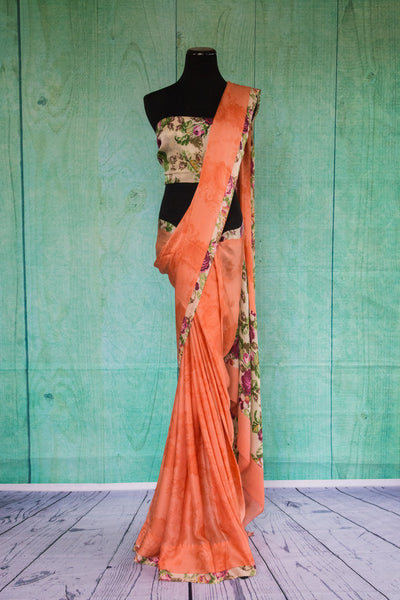 90c095 Alluring crepe saree in a lovely peachy-orange hue, with a floral trim and blouse. Buy this printed saree online in USA at Pure Elegance and add it to your Indian clothing collection today!