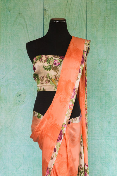90c095 Alluring crepe saree in a lovely peachy-orange hue, with a floral trim and blouse. This printed saree is available online in USA at Pure Elegance. Add it to your ethnic wardrobe today!