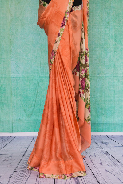 90c095 Traditional crepe saree in a lovely peachy-orange color, paired with a floral trim and blouse. Buy this printed saree online in USA at our store Pure Elegance.