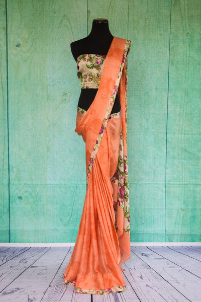 90c095 Alluring crepe saree in a lovely peachy-orange hue, with a floral trim and blouse. Buy this printed saree online in USA at Pure Elegance. This ethnic outfit will make for a a great addition to your Indian wear wardrobe.