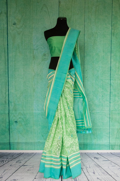 90c130 Light green traditional saree with teal border and ethnic paisley an floral pattern. Buy this Indian woven saree from Banaras online in USA at our ethnic fashion store Pure Elegance.