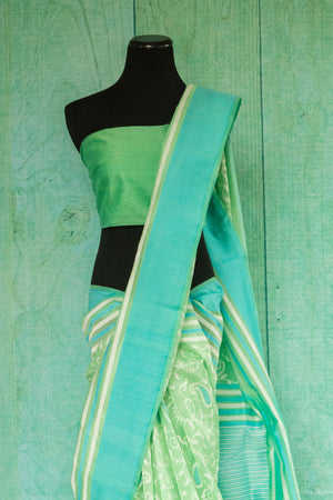90c130 Light green saree online in USA with teal border and ethnic paisley an floral pattern. Buy this traditional woven saree from Banaras at our store Pure Elegance.