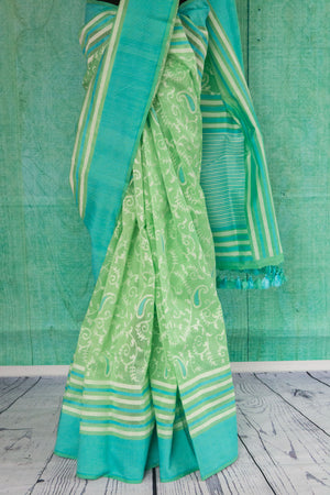90c130 Light green saree with a teal border and ethnic paisley an floral pattern. Buy this traditional woven saree from Banaras online at our store Indian clothing store in USA - Pure Elegance.
