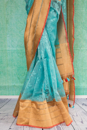 90c132 Traditional woven saree from Banaras in a stunning shade of teal blue with a gold border and an orange trim. The ethnic saree, available at Pure Elegance is ideal for festive occasions and pujas.