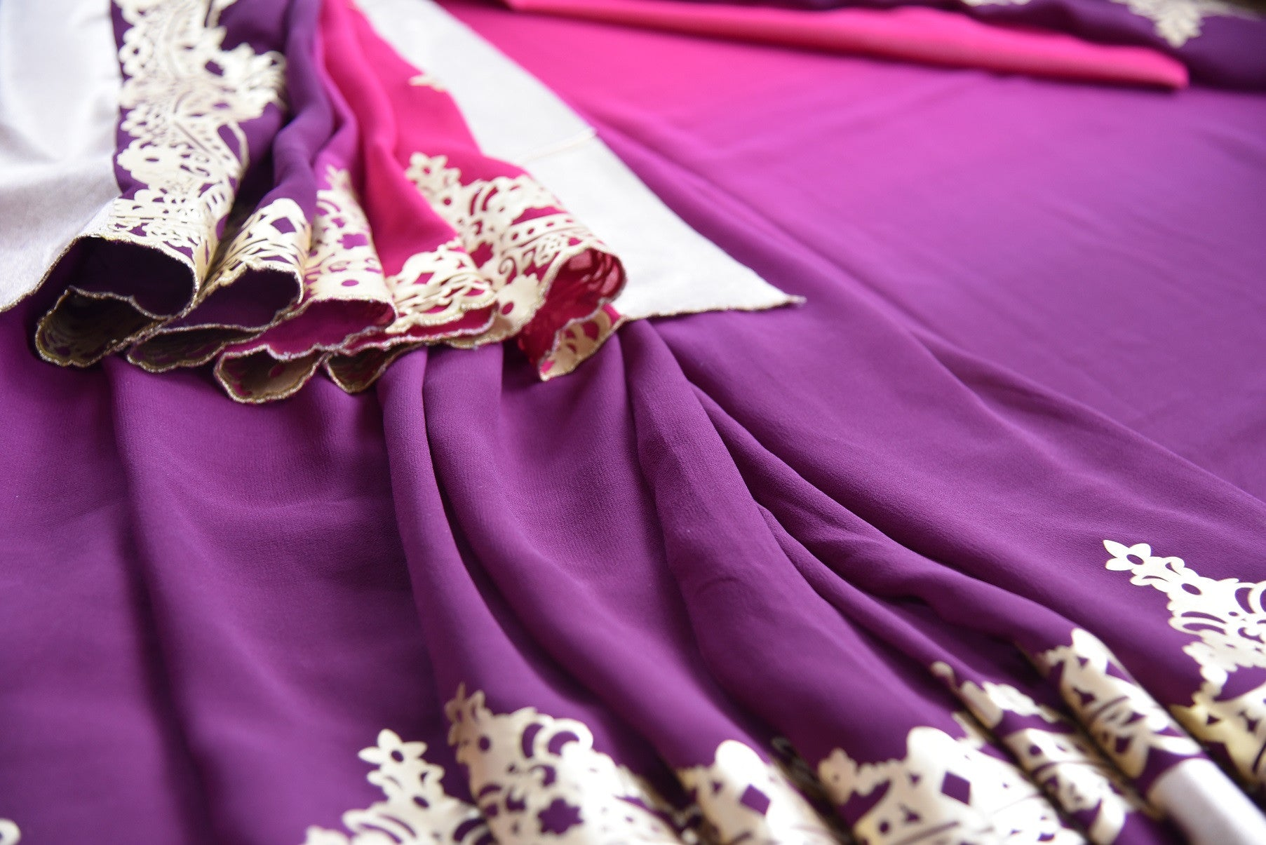 90c200 Shaded purple and wine red saree with exquisite leather work. The georgette party wear saree from India can be bought at our ethnic clothing store in USA. This one is a beautifully striking saree that is not to be missed!