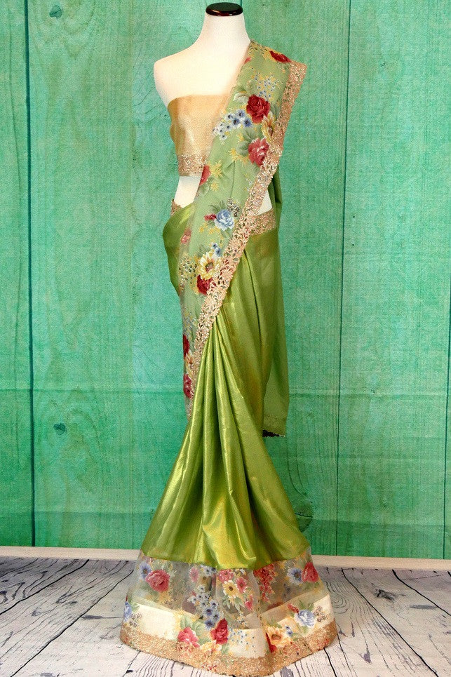 90c202 Looking for a party wear saree? Buy this green shimmer saree from India with a floral organza border online at our Indian clothing store in USA - Pure Elegance. This saree blends beauty and elegance with a hint of fun wonderfully well.