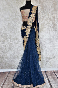 90c215 - This traditional blue sari comes with a heavily embroidered, golden border. The net chiffon saree can be bought online at our Indian ethnic wear store in USA and will be the perfect addition to your Indian outfits.