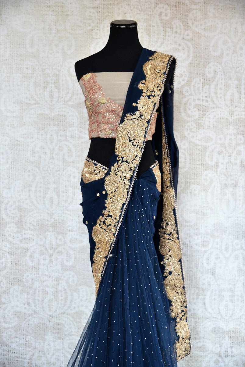 90c215 - This traditional blue sari comes with a heavily embroidered, golden border. The net chiffon saree can be bought online at our Indian ethnic wear store in USA and will an evergreen addition to your Indian wear wardrobe.