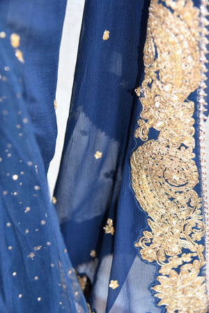 90c215 - This traditional blue sari comes with a heavily embroidered, golden border. The net chiffon saree can be bought online at our Indian ethnic wear store in USA and will be a great pick for parties and ethnic occasions.
