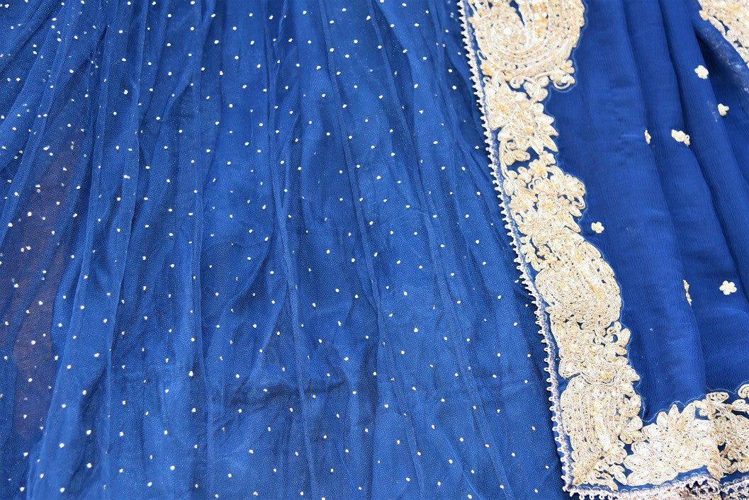 90c215 - This traditional blue sari comes with a heavily embroidered, golden border. The net chiffon saree can be bought online at our Indian ethnic wear store in USA and will be a versatile addition to your Indian fashion wardrobe.