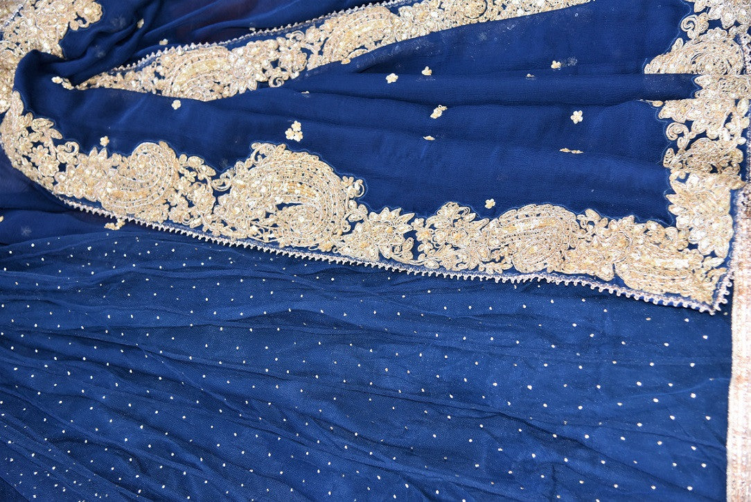 90c215 - This traditional blue sari comes with a heavily embroidered, golden border. The net chiffon saree can be bought online at our Indian ethnic wear store in USA. This classic saree is sure to turn heads wherever you go!