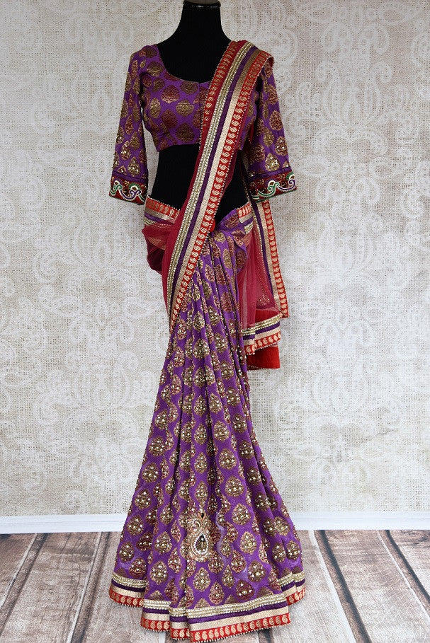 90C266 Traditional khaddi georgette saree with classic golden work. The red and purple embroidered sari makes for an evergreen Indian outfit for festive occasions and weddings. Buy this saree online at Pure Elegance.