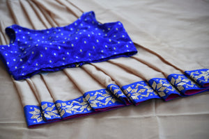 Buy beige saree online in USA with blue zircon border from Pure Elegance Indian fashion store in USA.-closeup