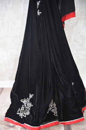 Black embroidered velvet saree with raw silk red and gold trim border.Perfect party saree for Indian evening parties.-pleats