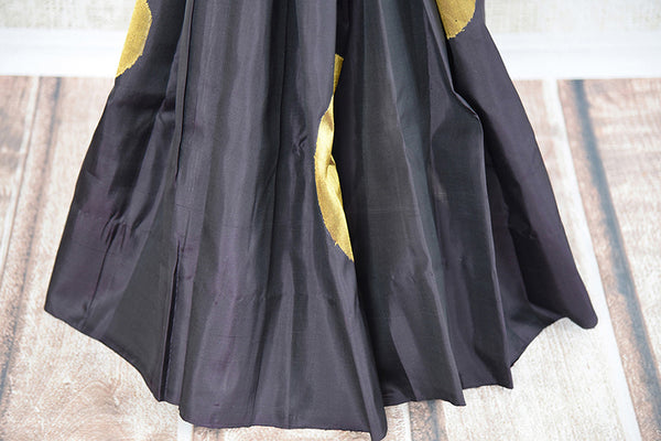 It's a woven black kanchipuram sari with thick gold border and buta. It has black blouse with gold border. Perfect traditional sari for party, festive occasion. bottom view