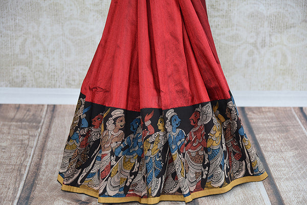 It's raw silk red kalamkari printed sari with black blouse. Has figure in back of the blouse and in the border. It has thin yellow border. Perfect for party. bottom view
